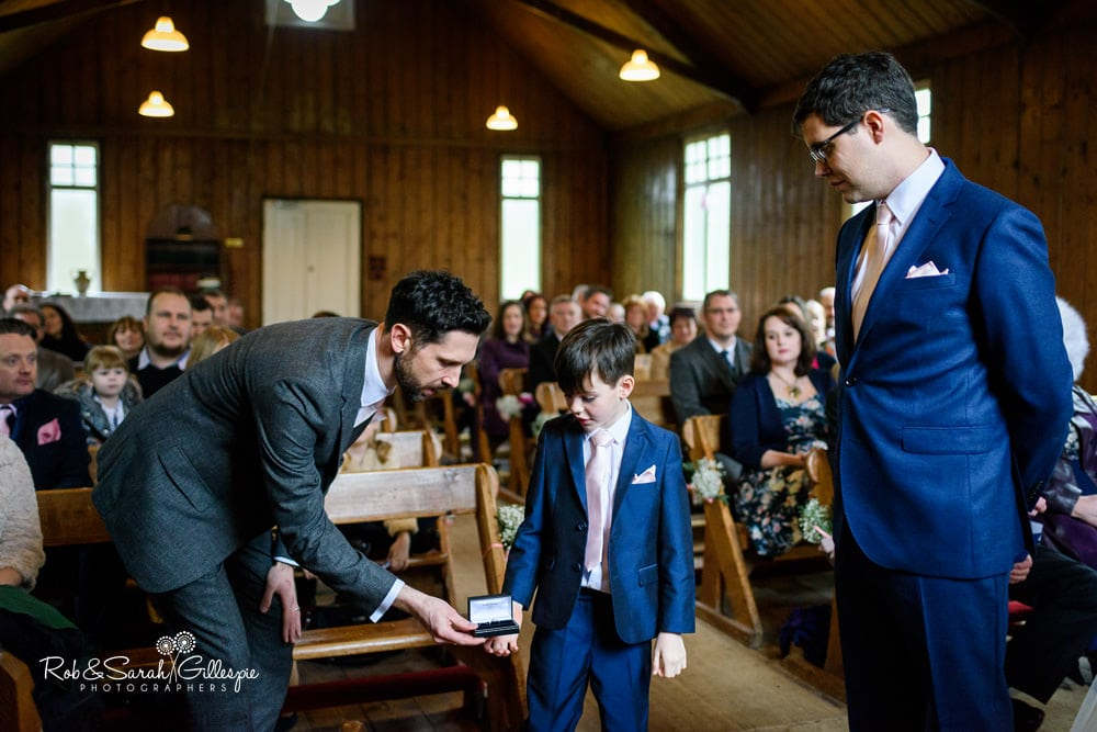 Best man gives wedding rings to pageboy during wedding blessing at Mission Church