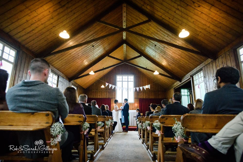 Bride and groom exchange wedding rings in Mission Church at Avoncroft Museum