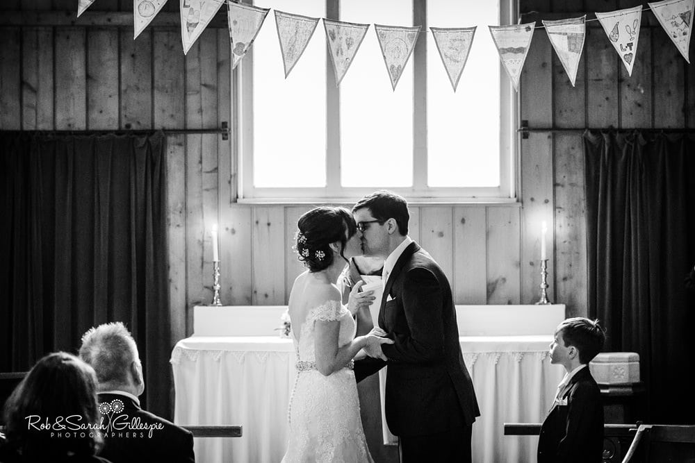 Bride and groom kiss in Mission Church at Avoncroft Museum