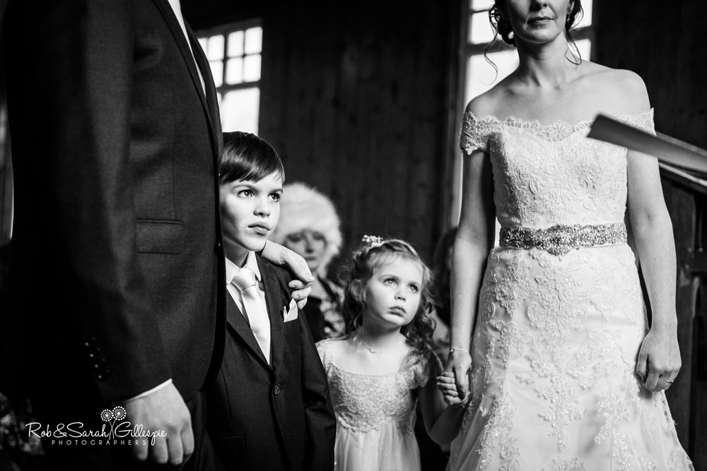 Pageboy and flowergirl listen to vicar during wedding blessing at Mission Church, Avoncroft Museum