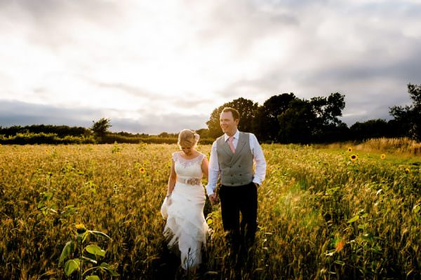 Bride and groom walk through field at Wethele Manor