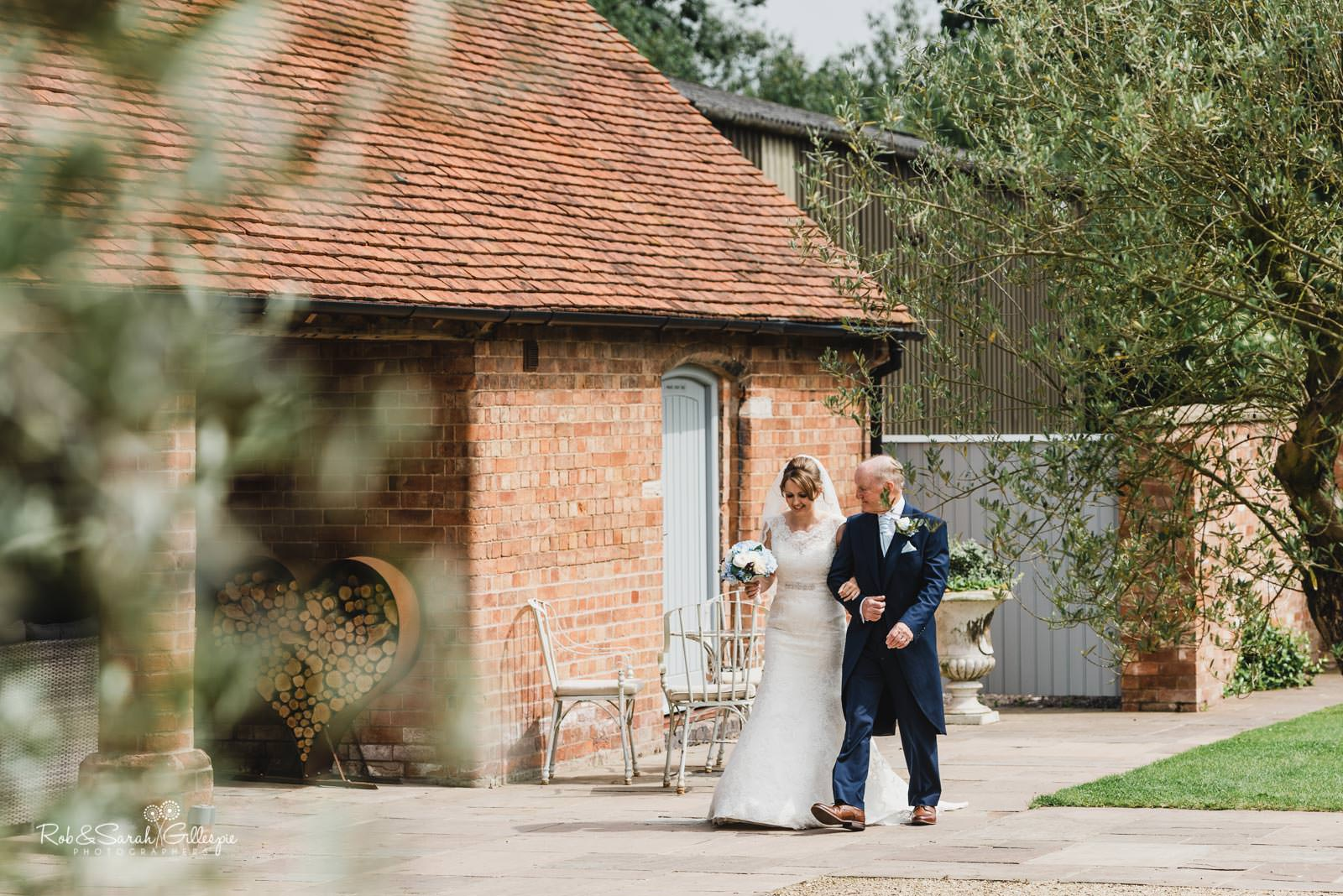Bride and father walk to ceremony at Wedding ceremony at Swallows Nest Barn wedding