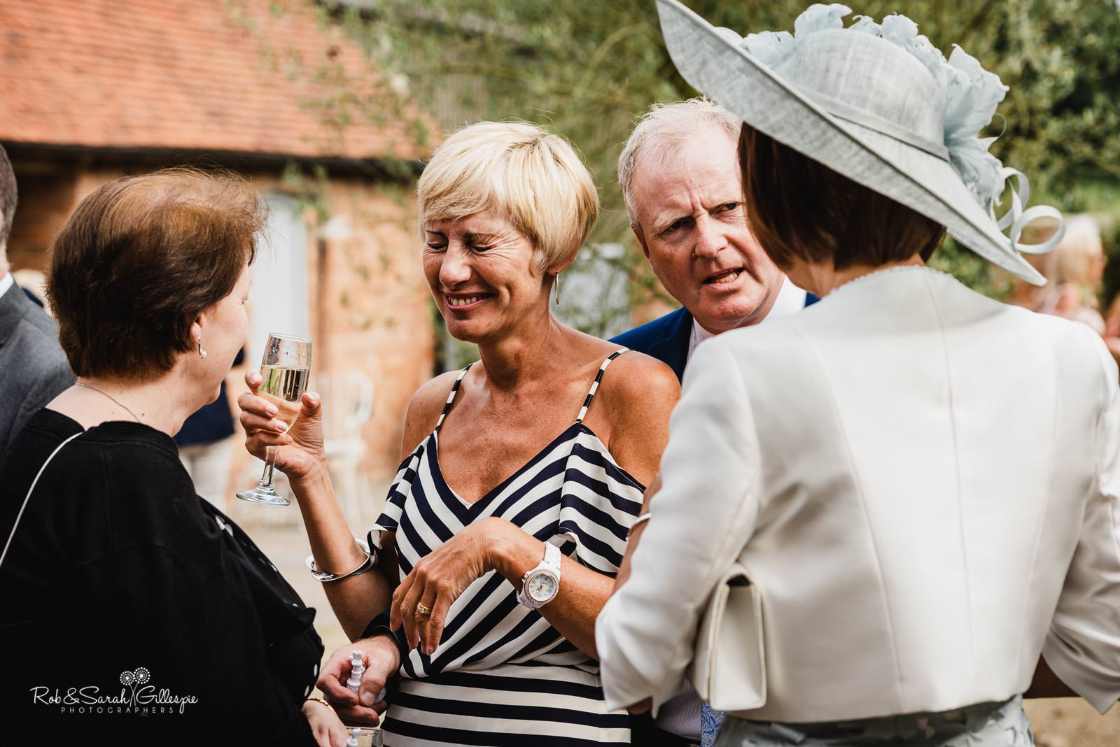 Wedding guests relax during drinks reception at Swallows Nest Barn
