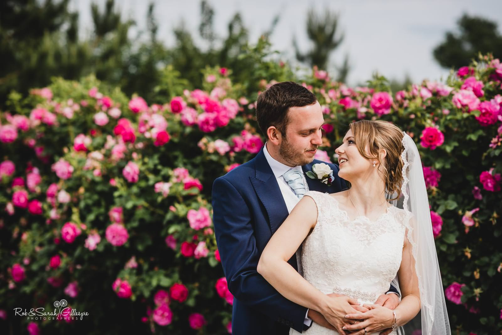 Bride and groom at Swallows Nest Barn wedding with garden flowers