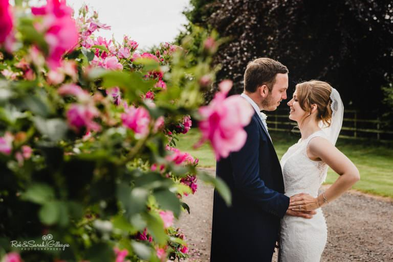 Bride and groom at Swallows Nest Barn with pink flowers