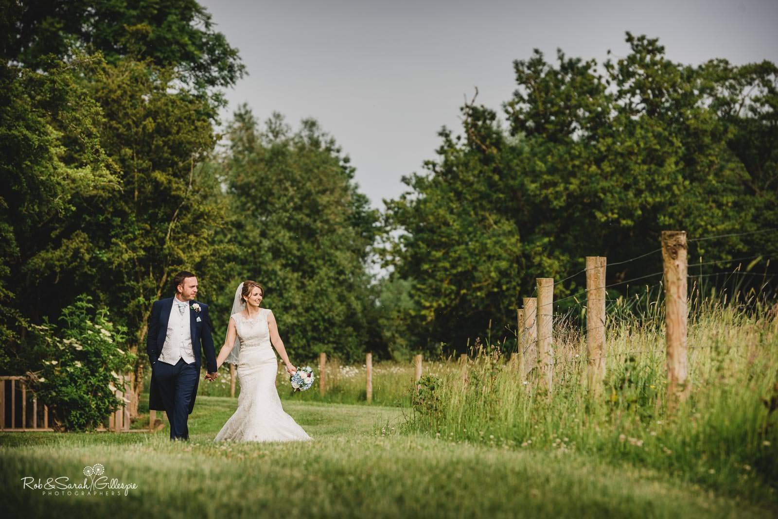 Bride and groom walk through grounds at Swallows Nest Barn