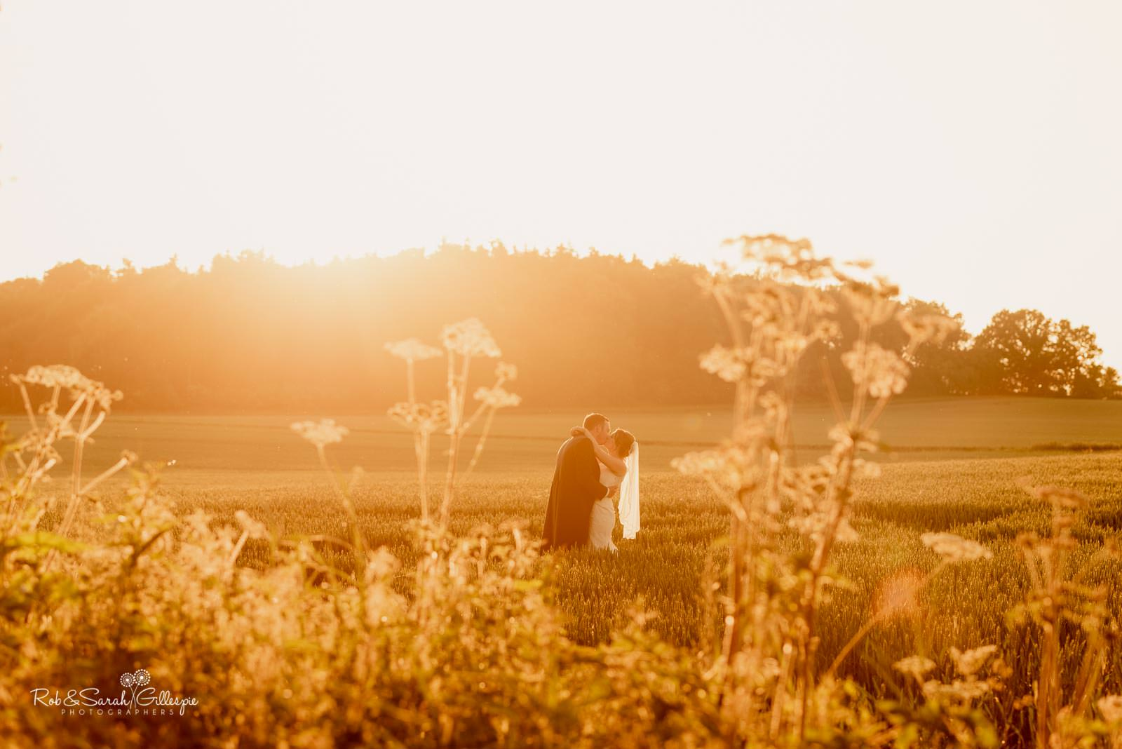 Bride and groom in fields at Swallows Nest Barn with beautiful light
