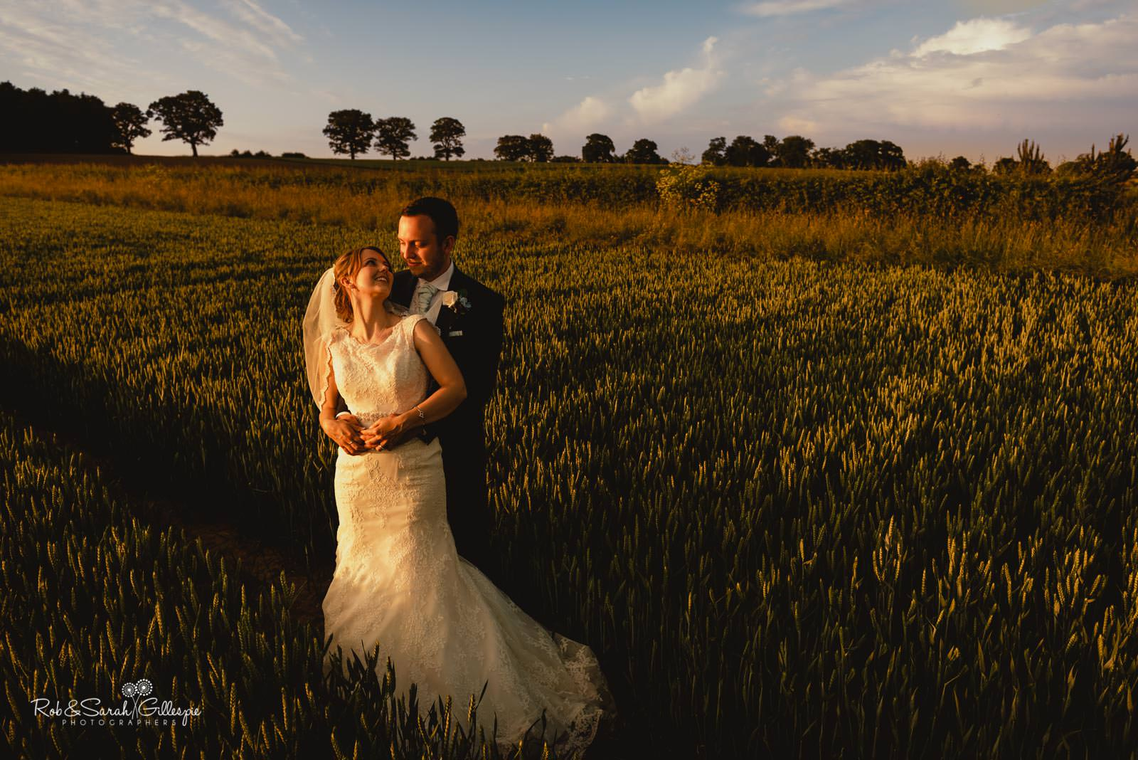 Bride and groom in fields at Swallows Nest Barn
