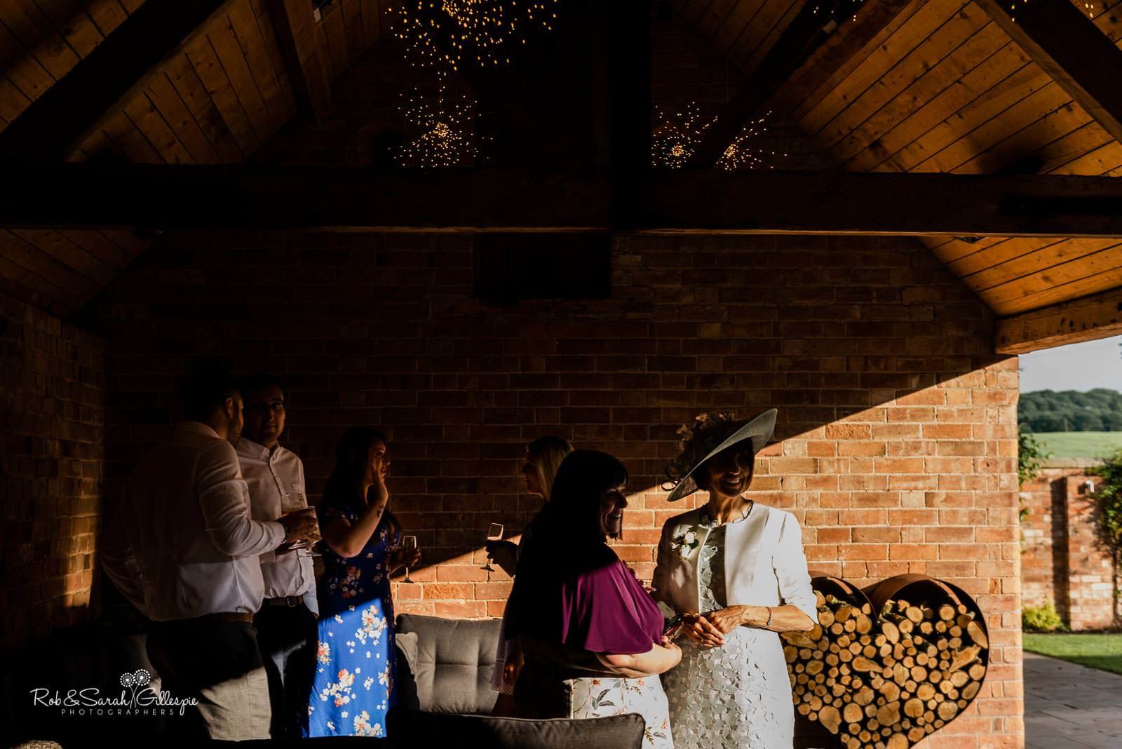 Wedding guests in evening light at Swallows Nest Barn