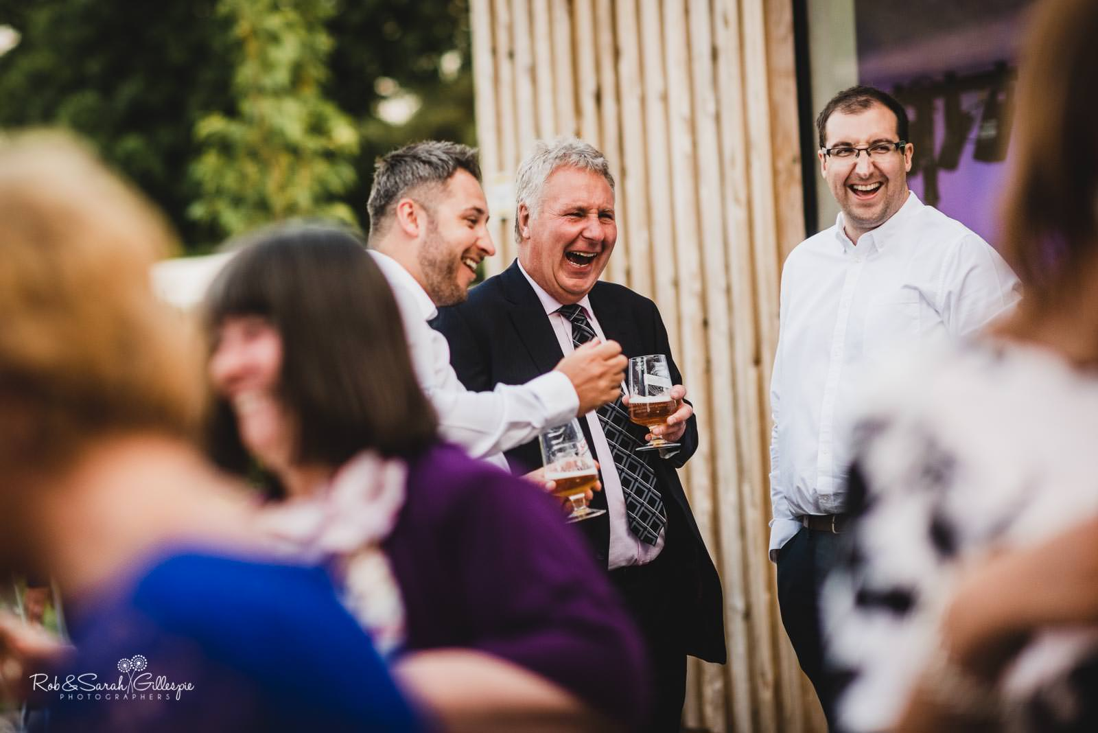 Wedding guests laughing at Swallows Nest Barn