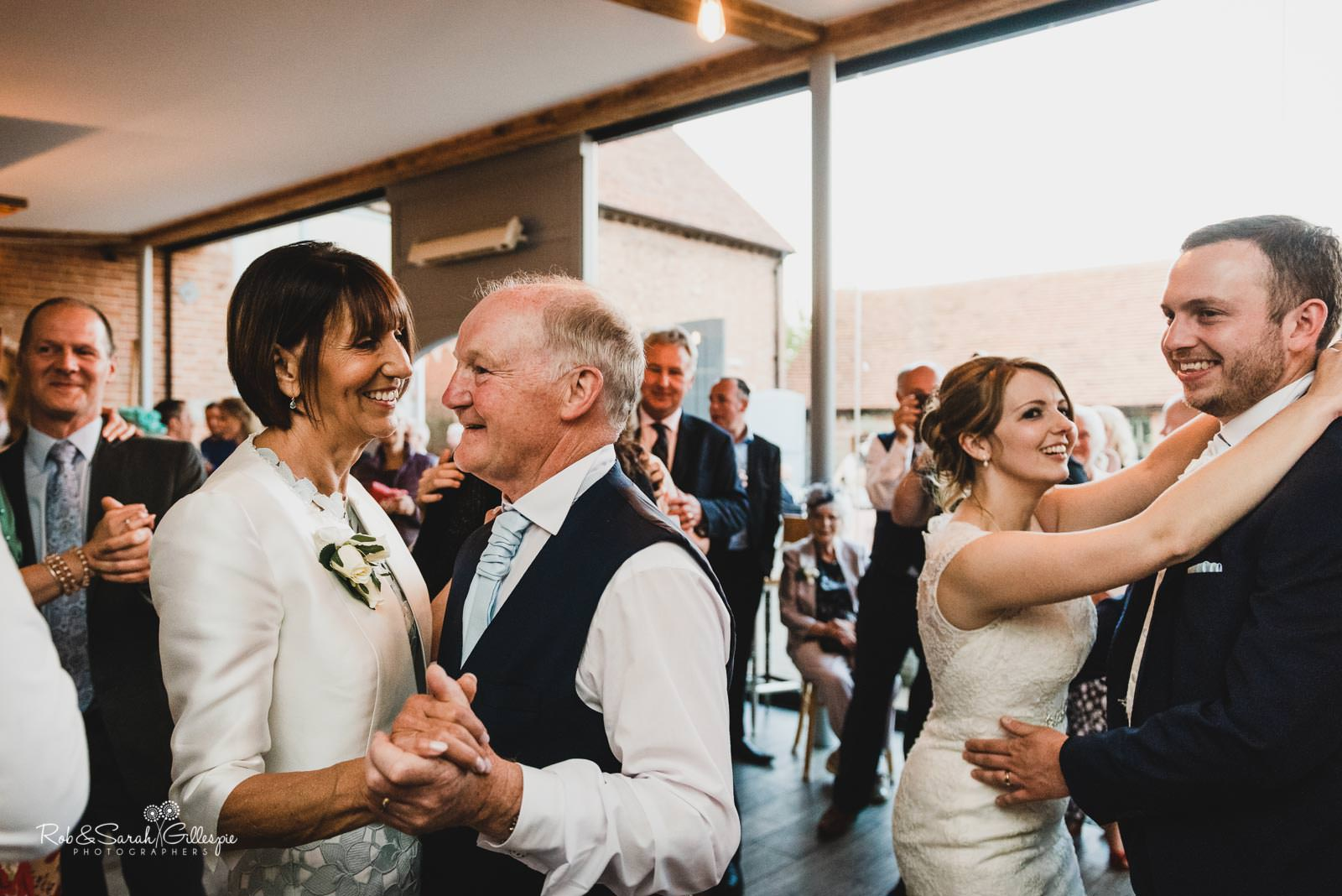 Bride, groom and guests dancing at Swallows Nest Barn wedding