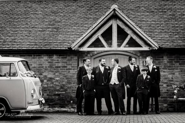 Groomsmen line up for photo outside Swallows Nest Barn