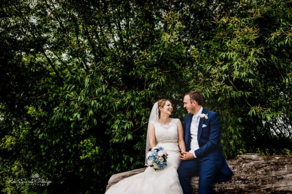 Bride and groom sitting on log relaxing
