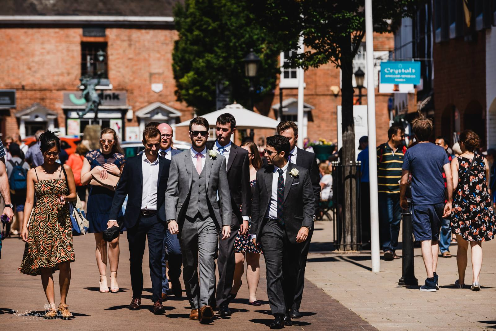 Groom and friends walk through Stratford upon Avon town centre