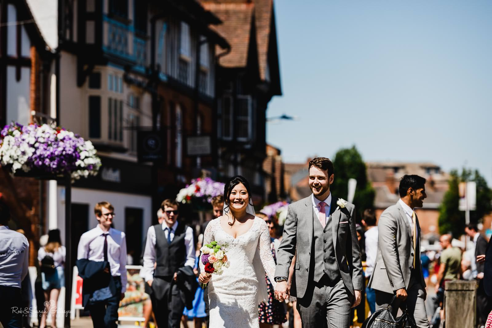 Bride, groom and wedding guests walk through Stratford upon Avon town centre