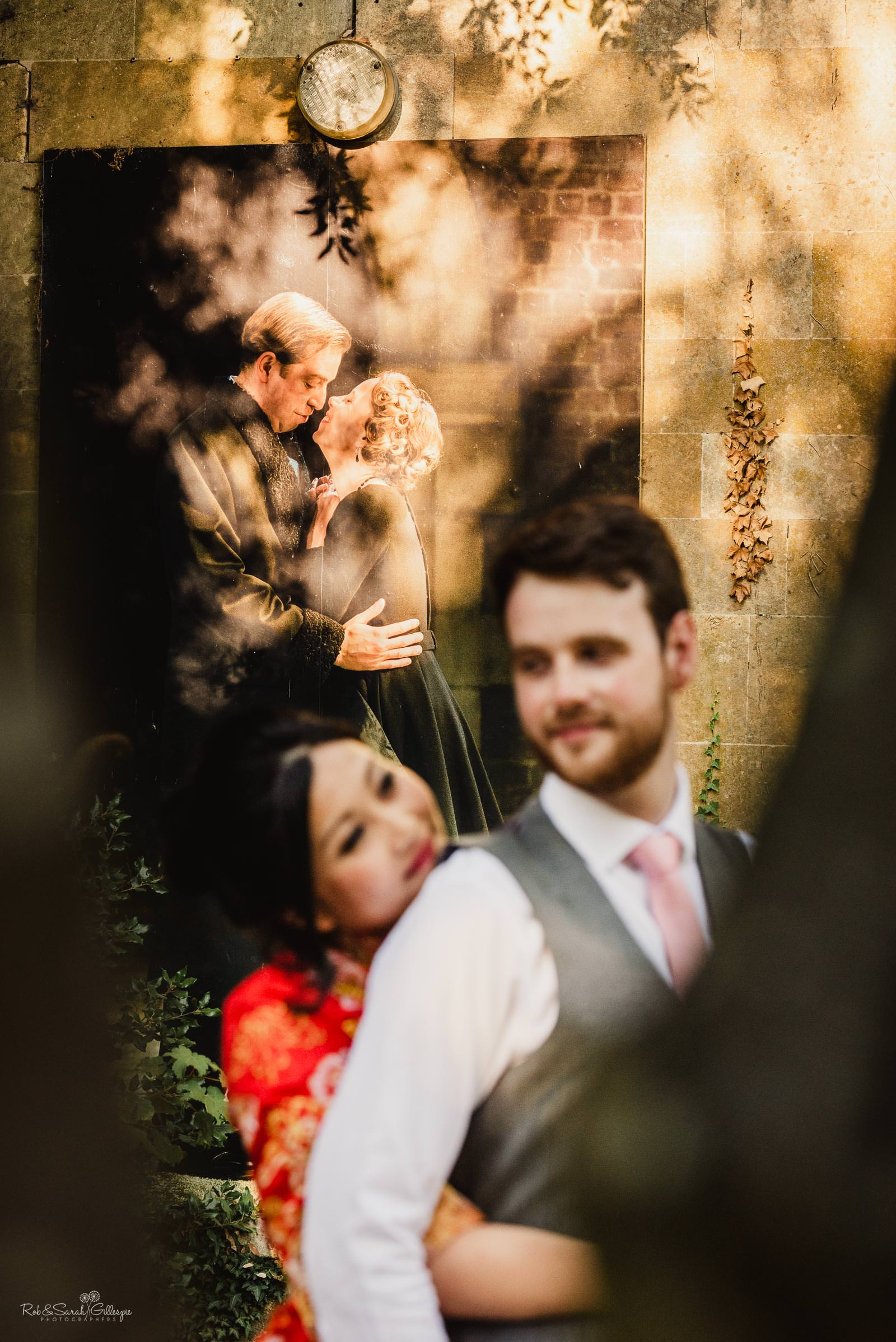 Bride and groom in Stratford upon Avon park with Shakespeare poster