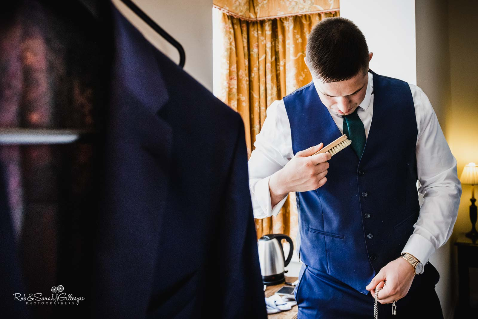 Groomsman brushes waistcoat preparing for wedding at Wethele Manor