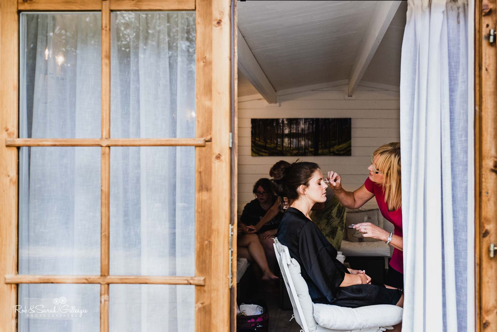 Bride has makeup applied in chalet at Wethele Manor