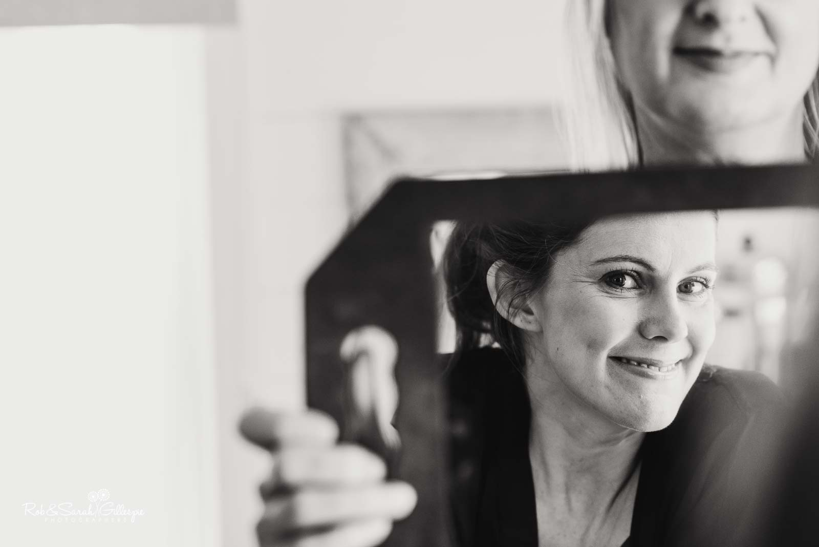 Bride smiling in mirror as she prepares for wedding at Wethele Manor
