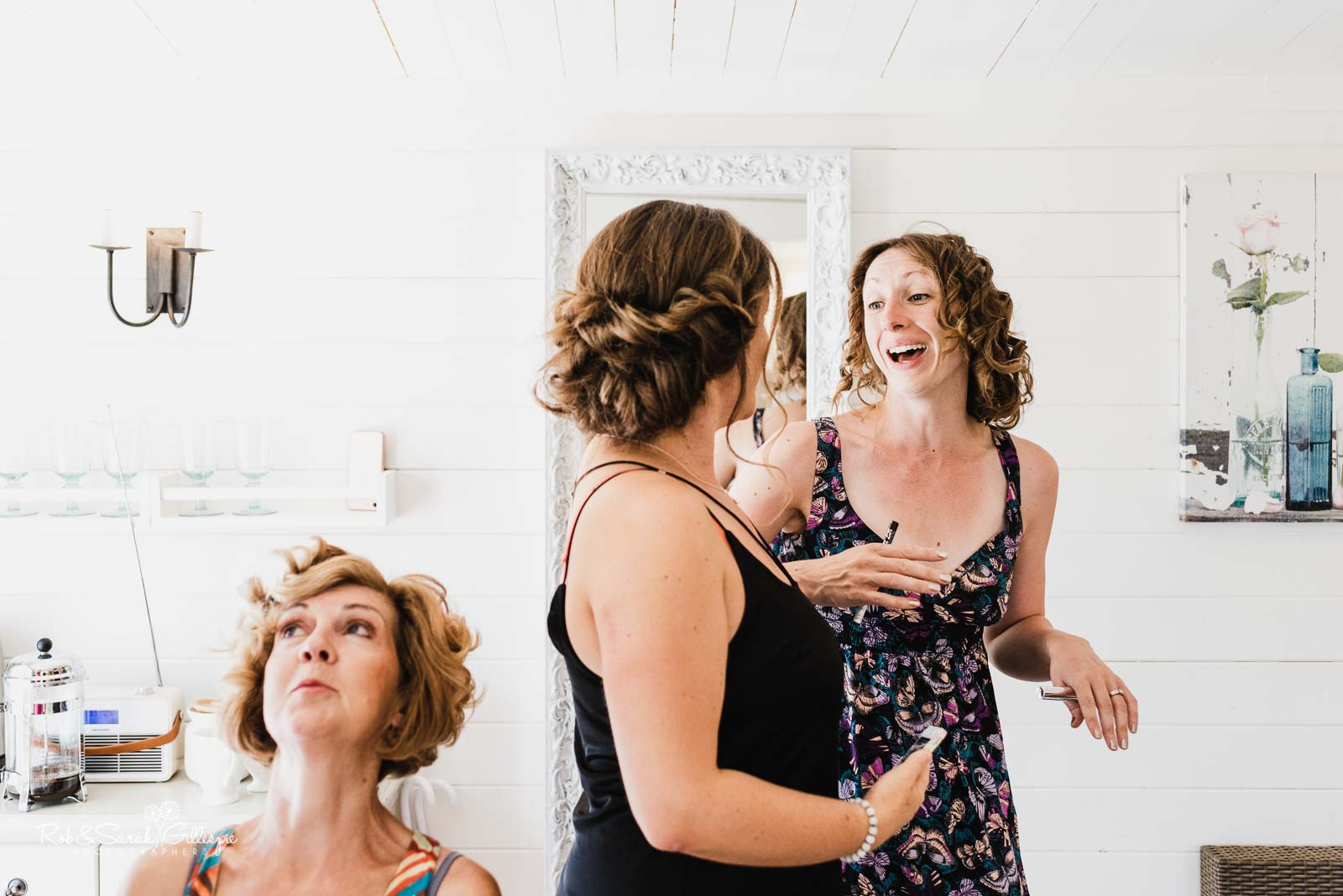Bridesmaids laughing as they prepare for wedding at Wethele Manor