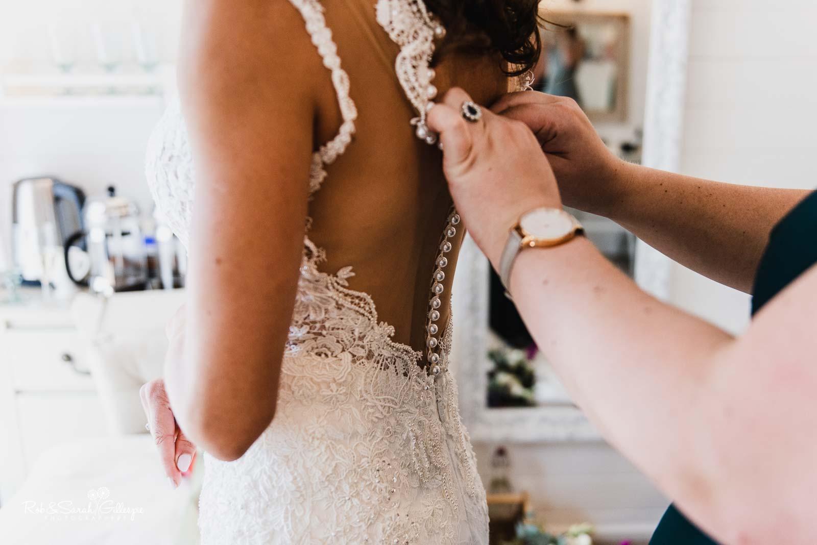 Bride has wedding dress fastened at Wethele Manor