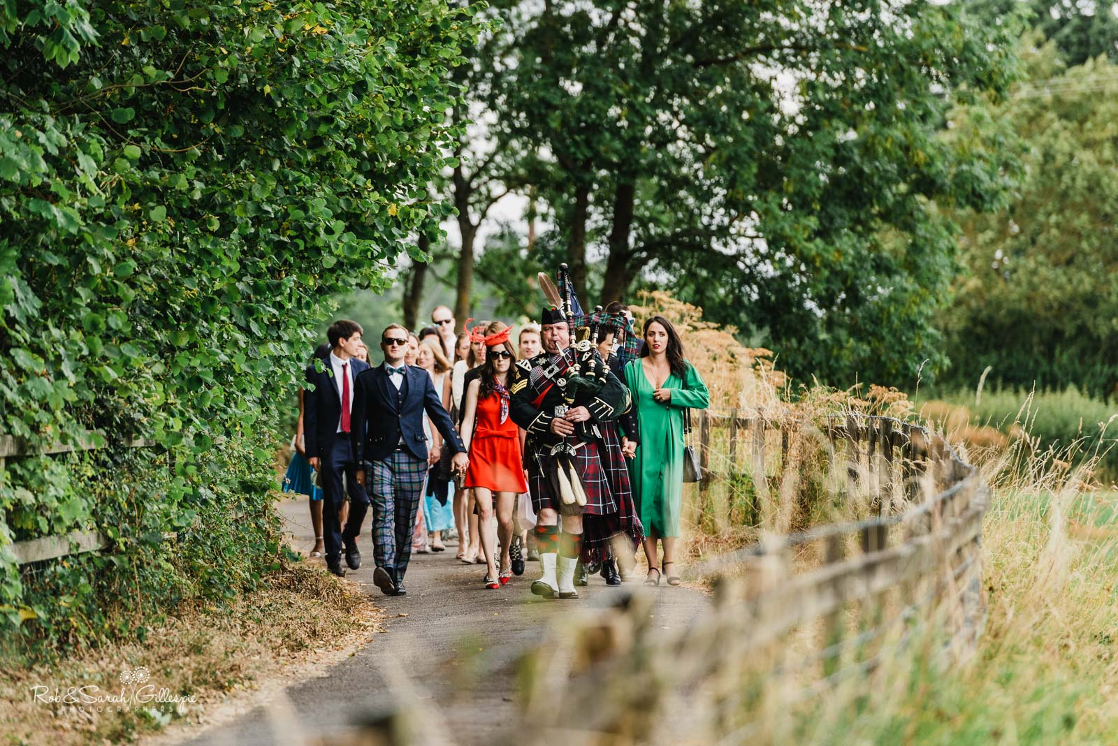 Wedding guests arrive at St Giles church Packwood accompanied by piper