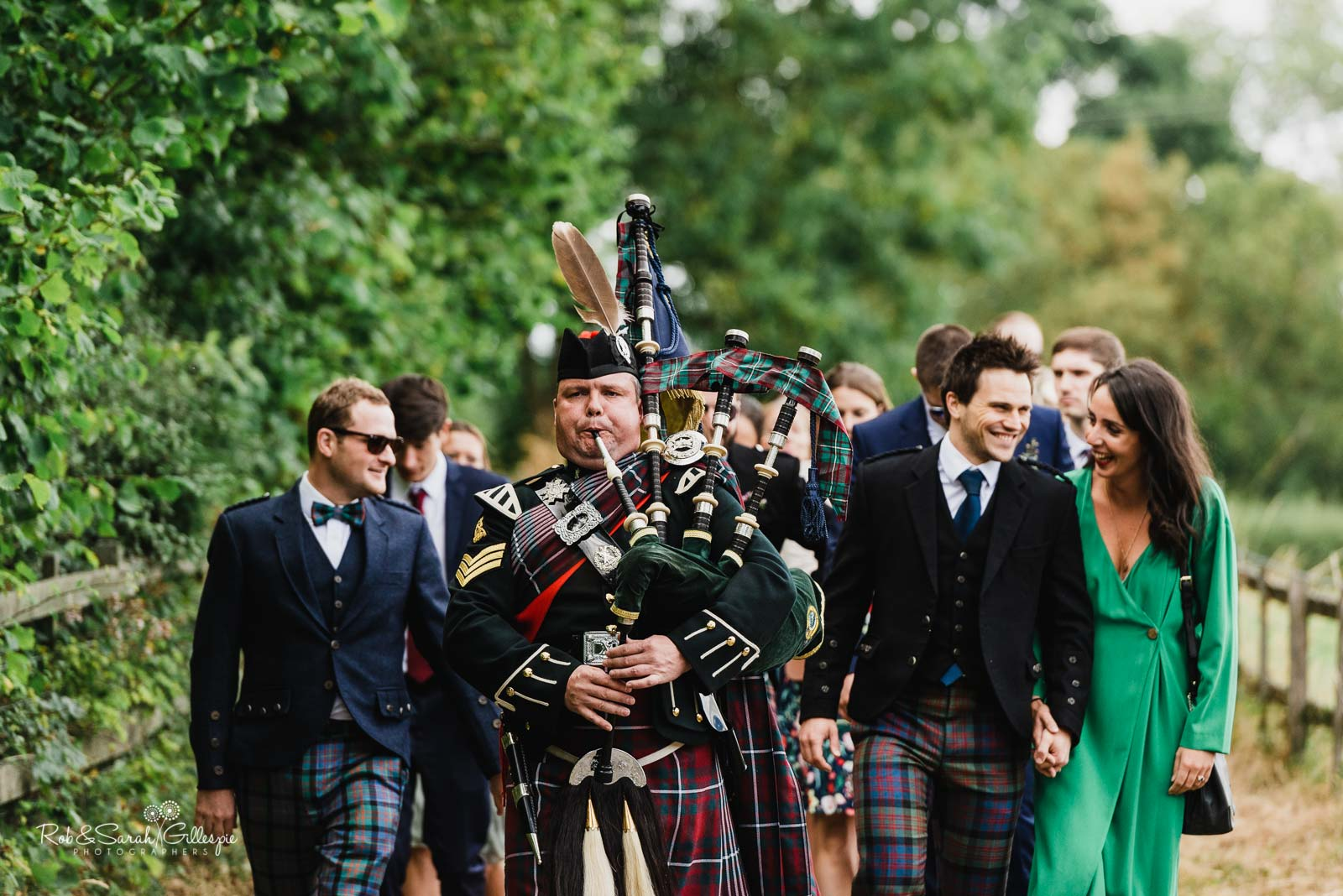 Wedding guests at St Giles church Packwood with piper