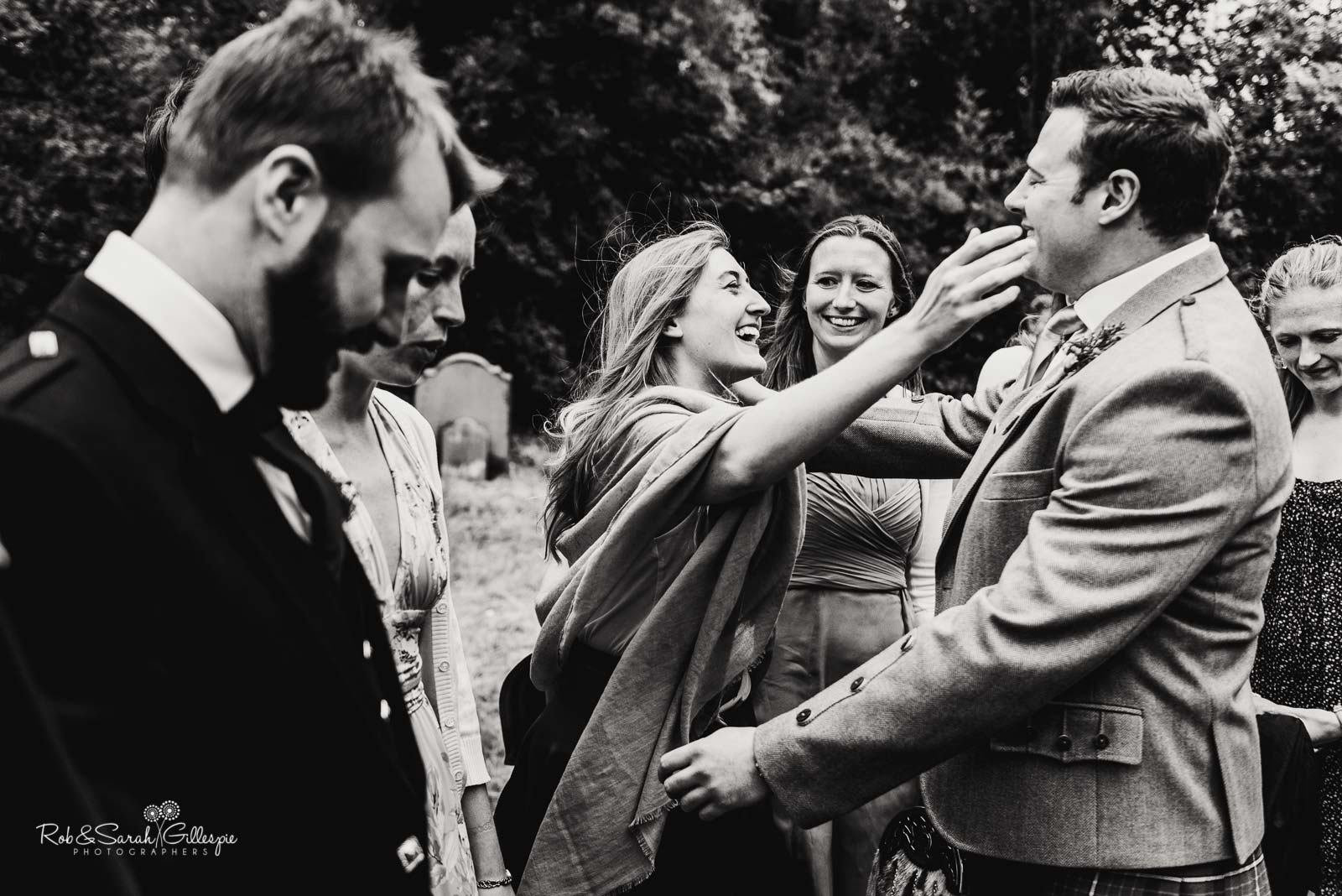 Groom greets wedding guests at St Giles church Packwood