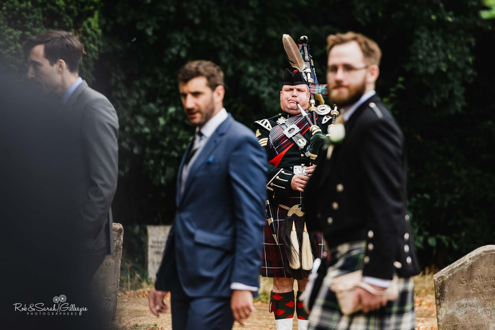 Piper plays bagpipes at St Giles church Packwood wedding