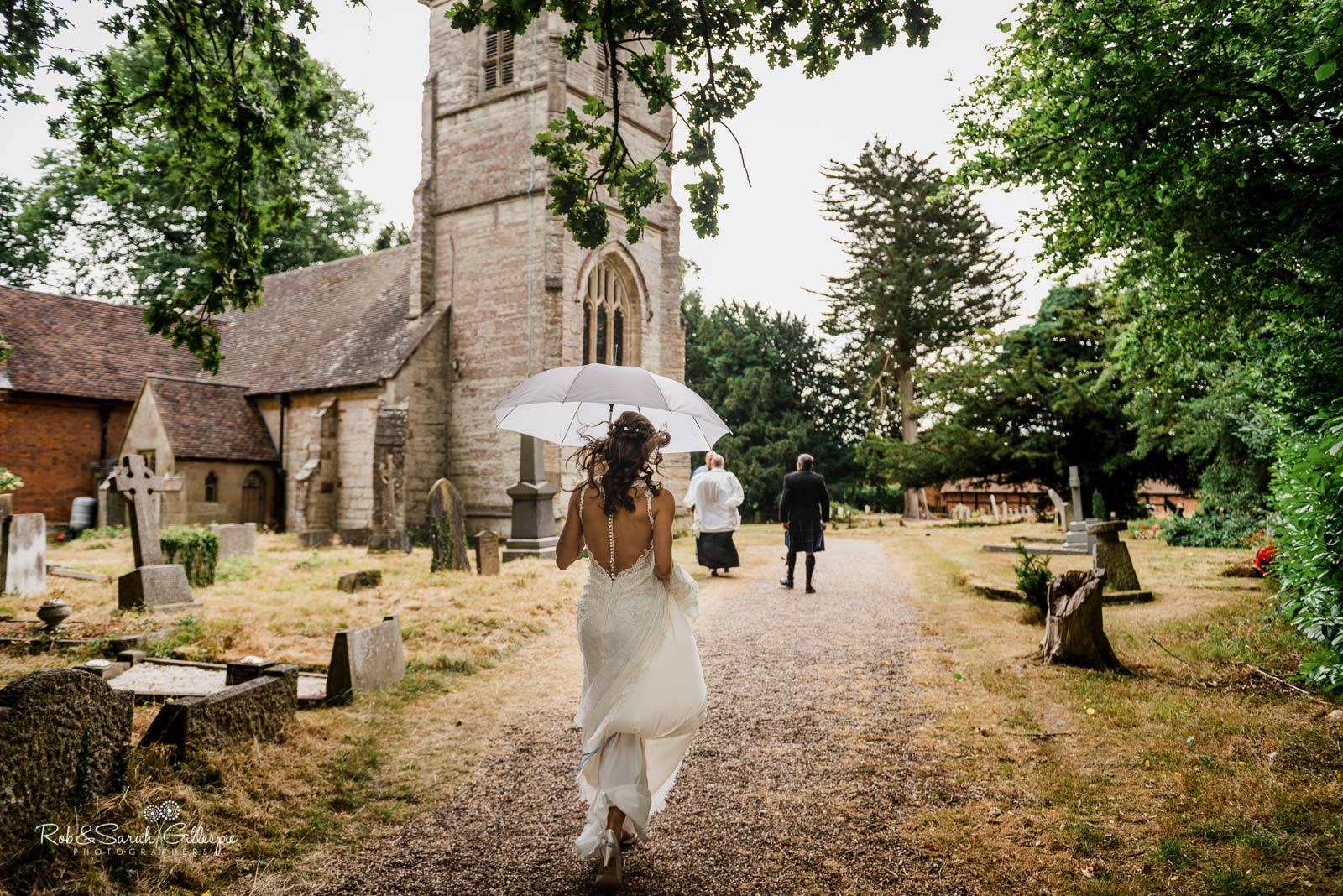 Bride walks to wedding at St Giles church Packwood