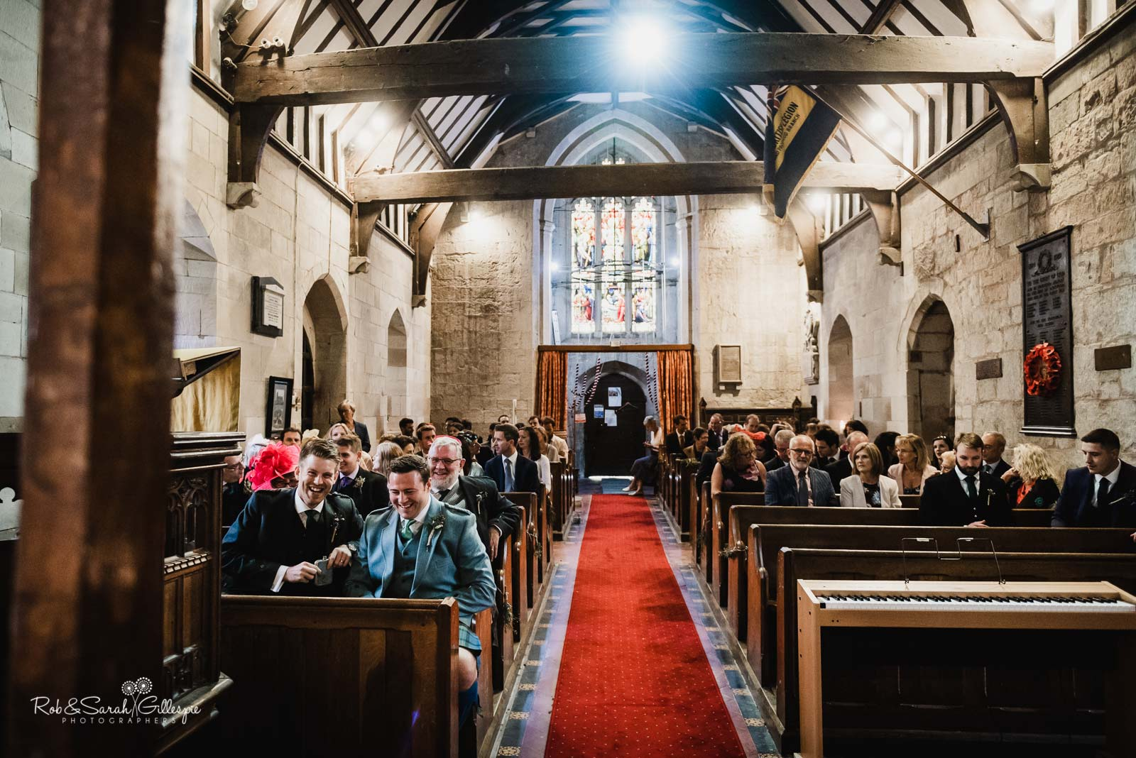 Wedding guests wait for bride to to arrive at St Giles church Packwood