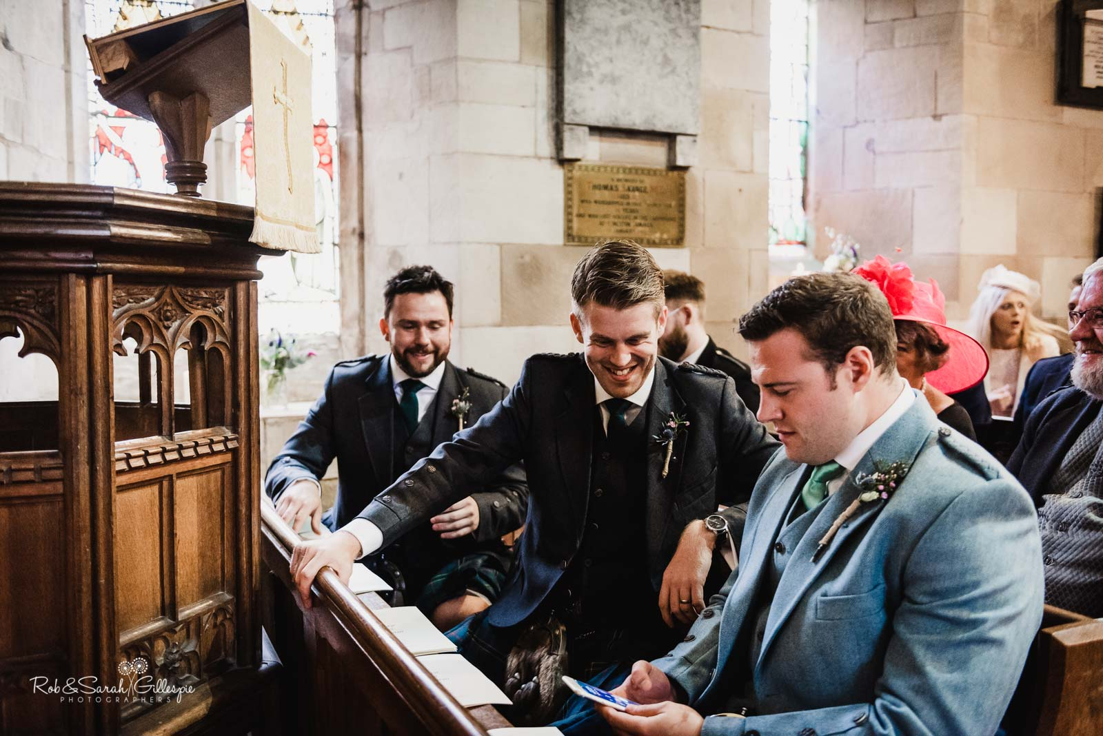Groom chats with friends before wedding at St Giles church Packwood