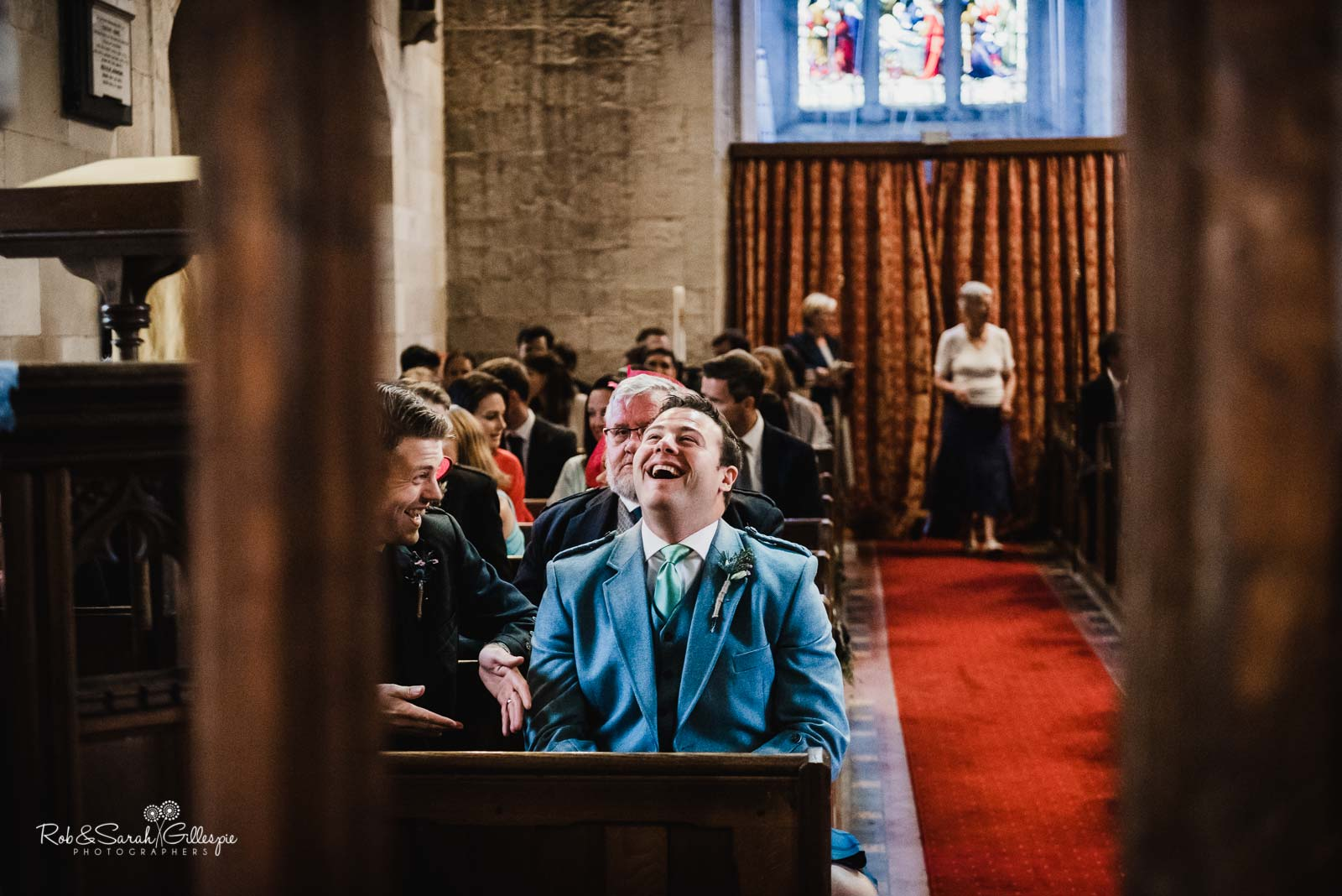 Groom laughs with friends before wedding ceremony at St Giles church Packwood