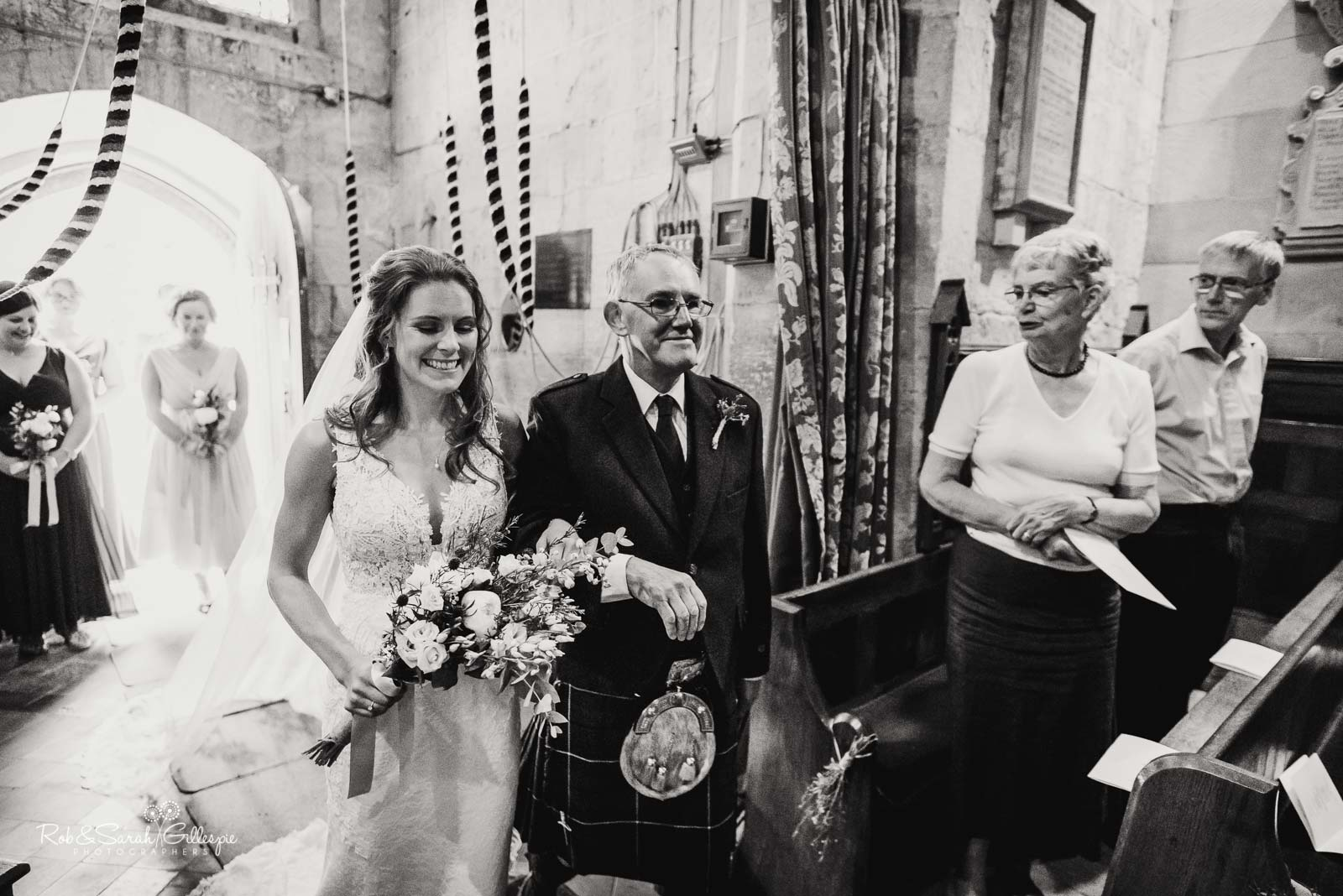 Bride and father make entrance at St Giles church Packwood