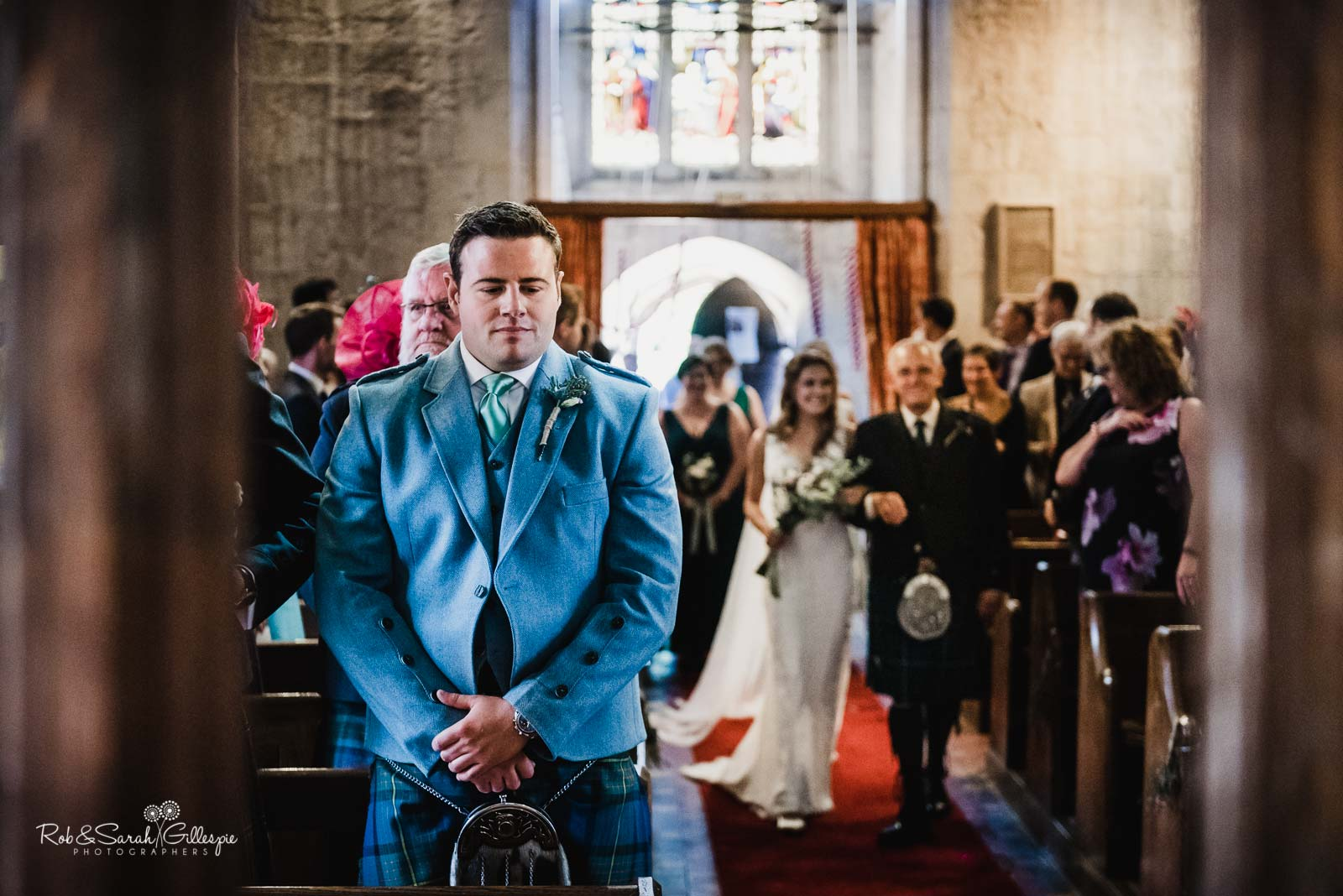 Groom waits for bride at end of aisle at St Giles church Packwood