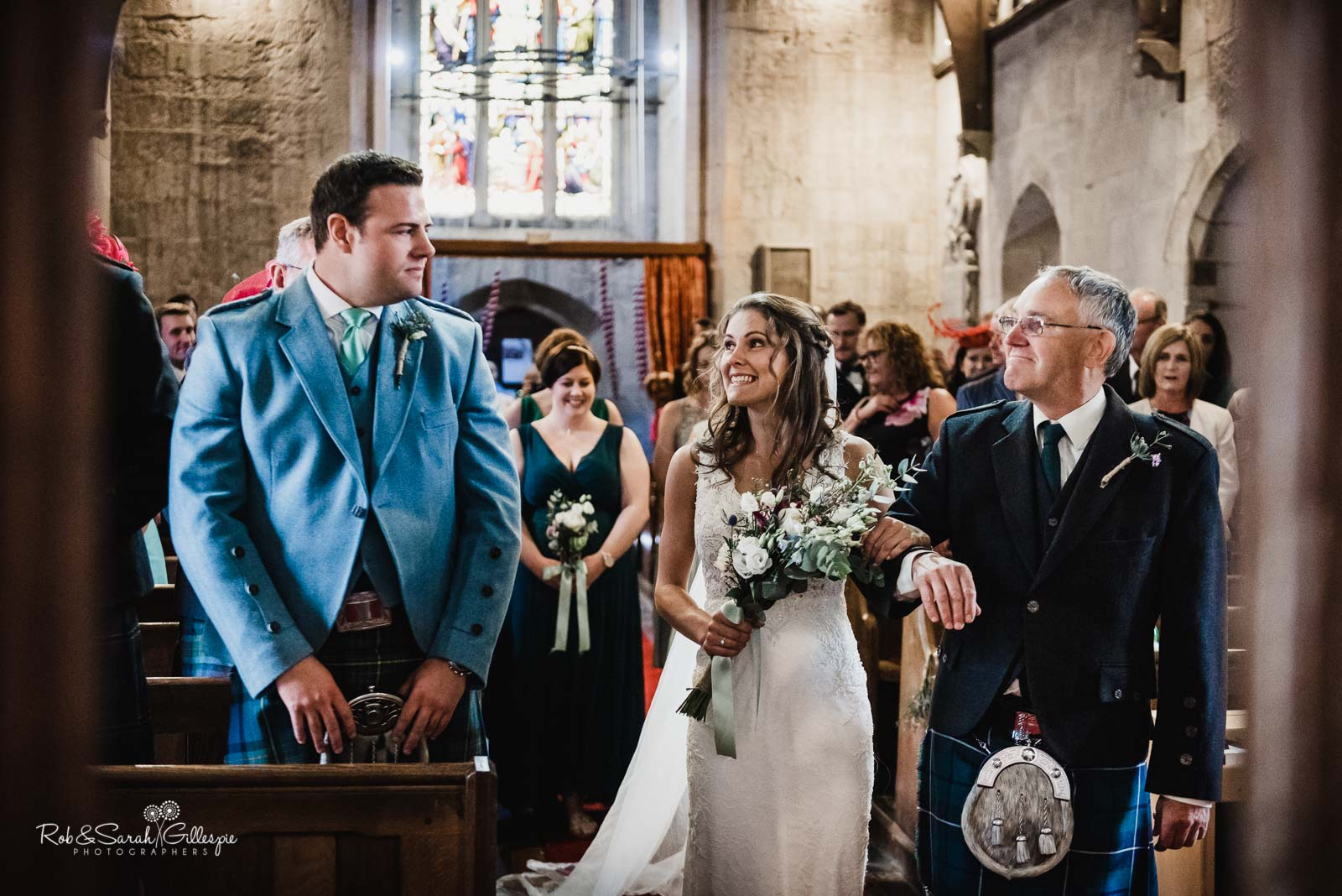 Bride and groom smiling at each other at St Giles church Packwood