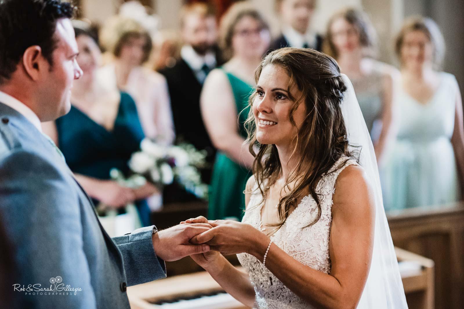 Bride and groom exchange rings at St Giles church Packwood wedding