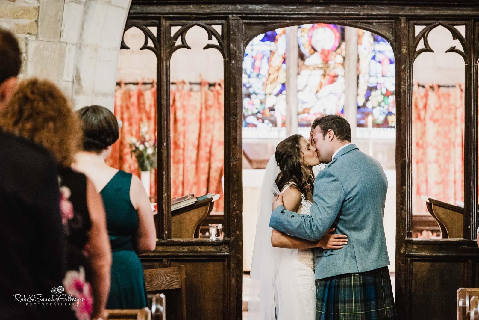 Bride and groom kiss during wedding ceremony at St Giles church Packwood