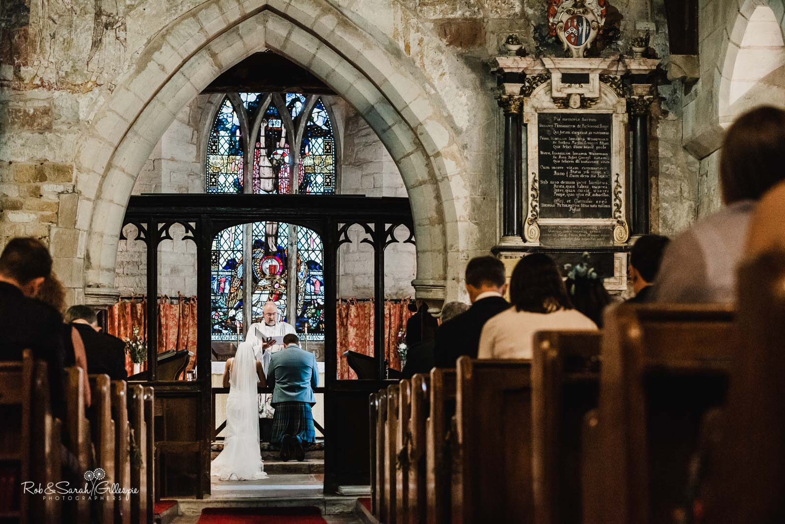 Bride and groom blesses by vicar during wedding at St Giles church Packwood