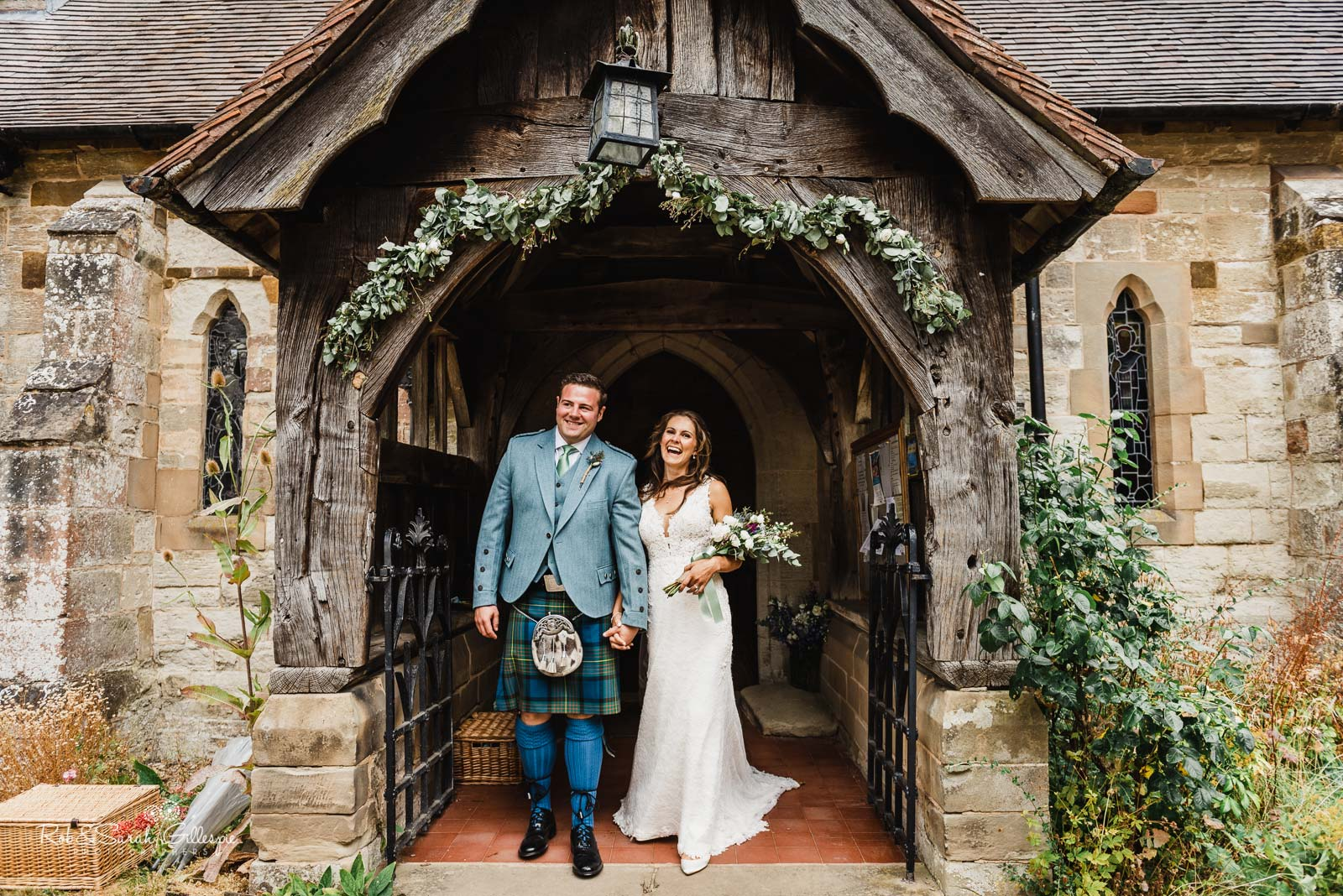 Bride and groom in doorway at St Giles church Packwood