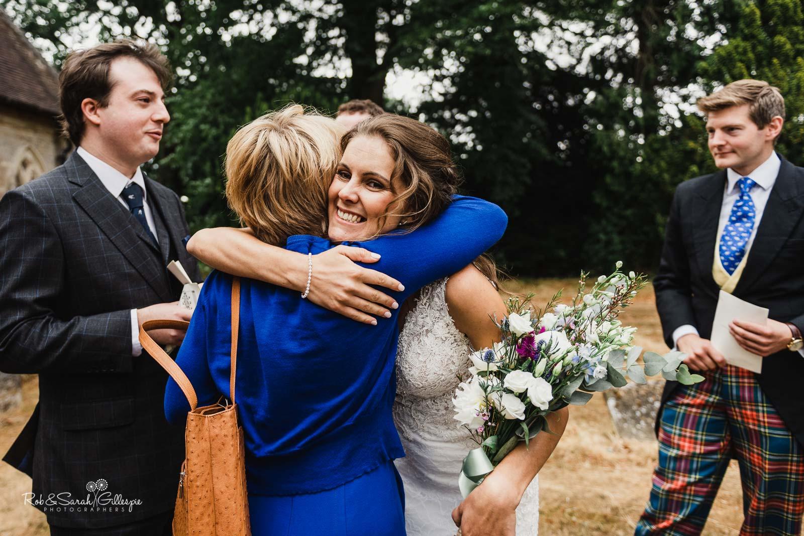 Bride hugs wedding guests at St Giles church Packwood