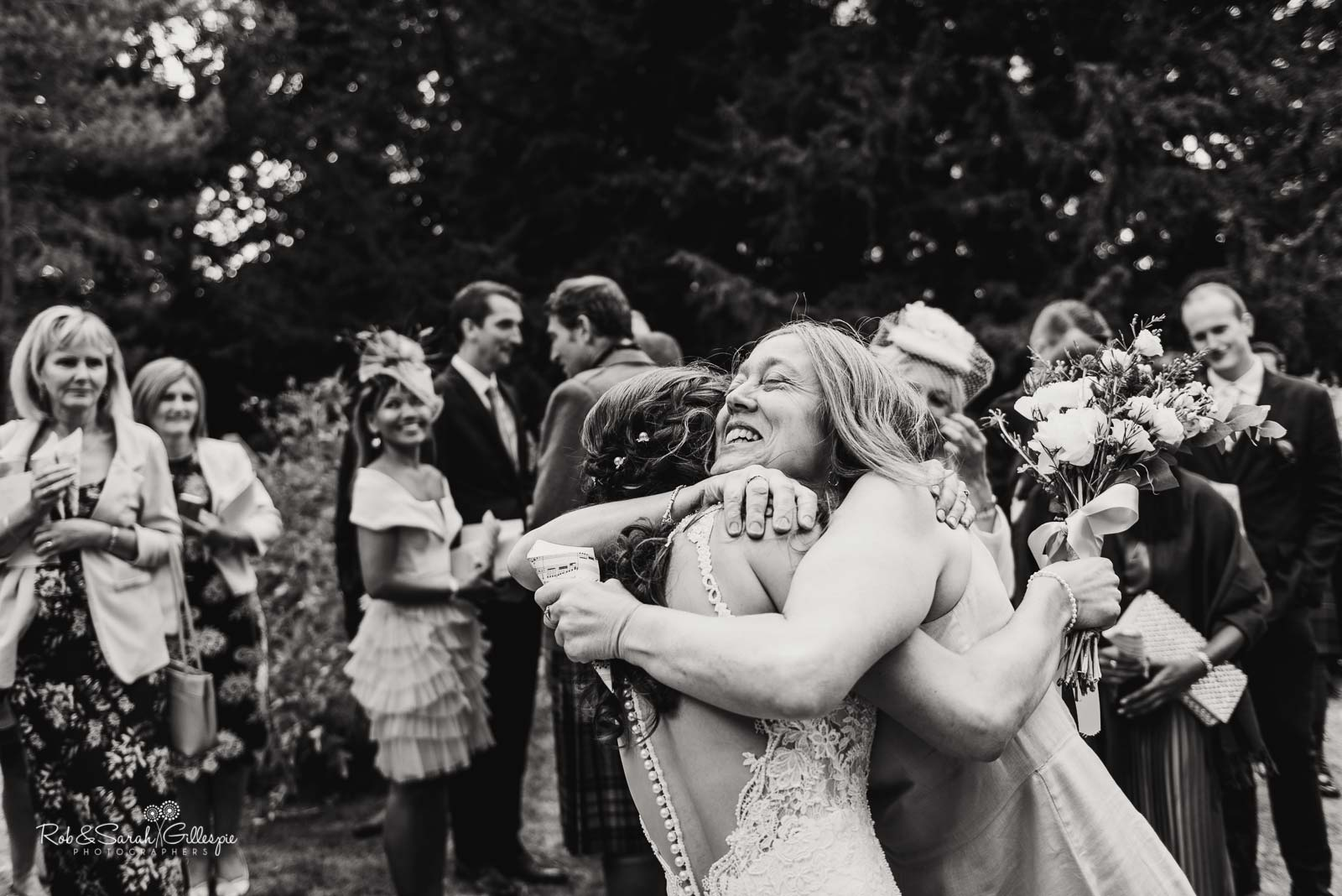 Bride and guest hug at St Giles church Packwood wedding