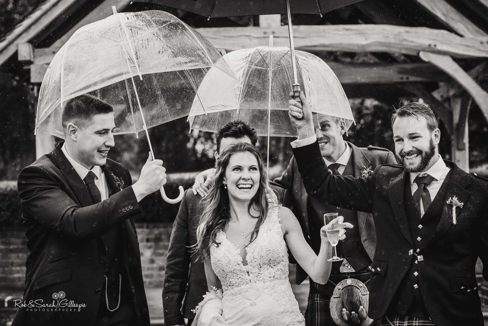 Bride laughing with friends under umbrellas at Wethele Manor