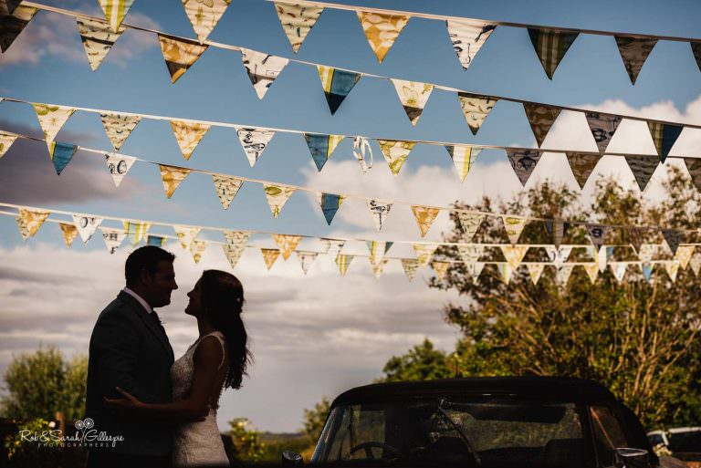 Bride and groom under bunting at Wethele Manor
