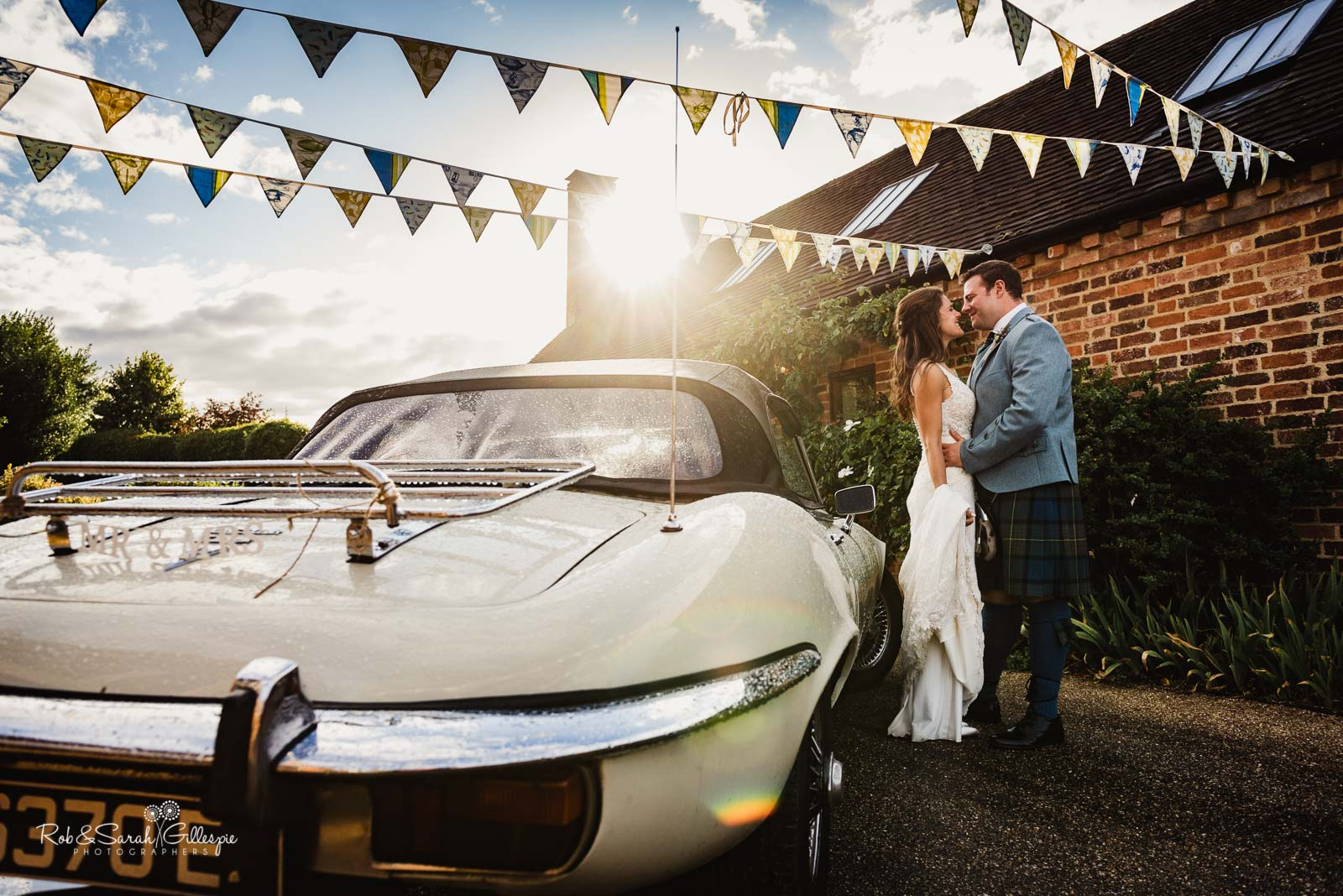 Bride and groom at Wethele Manor with sports car and bunting