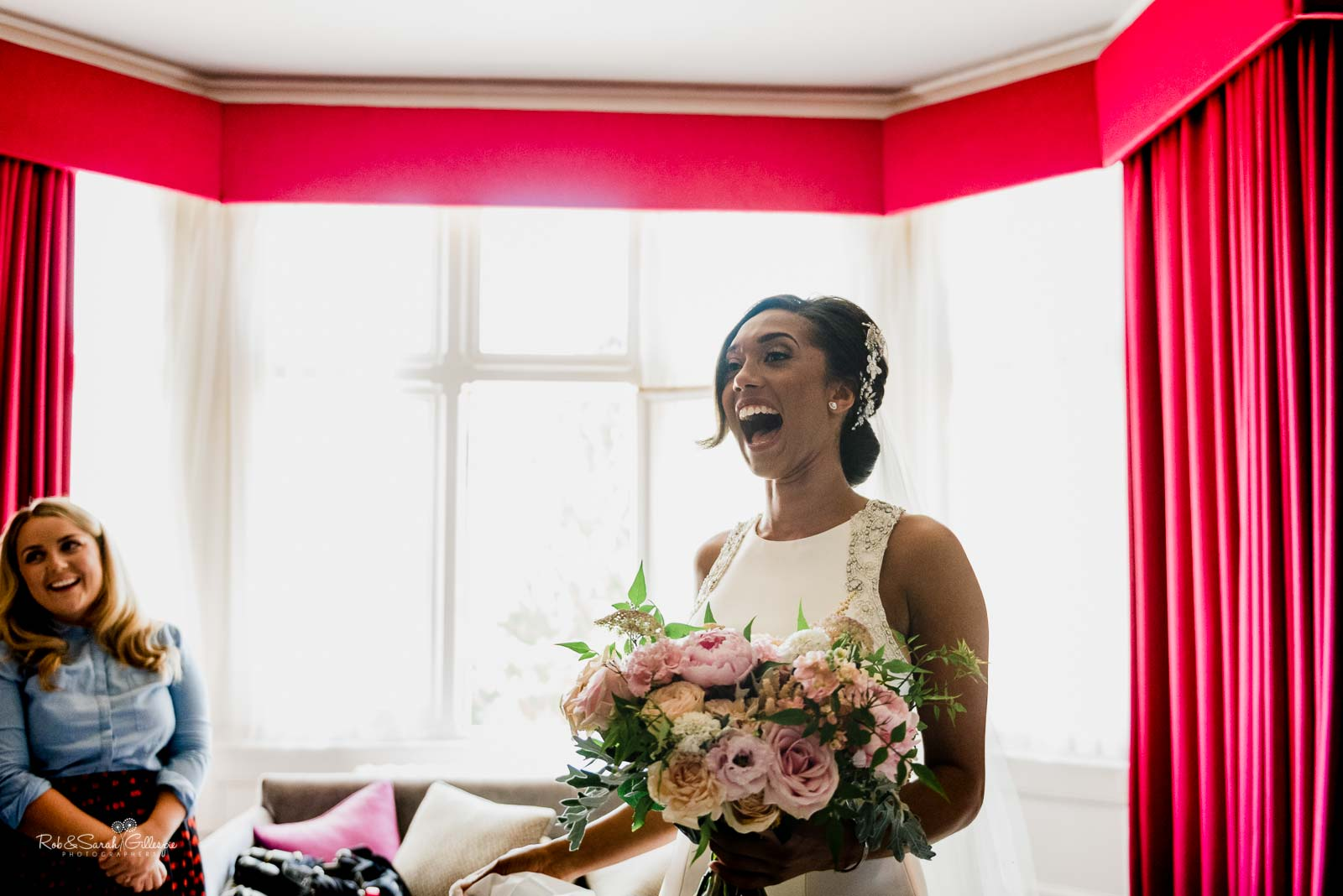 Bride laughing as her father sees her in wedding dress at Hampton Manor