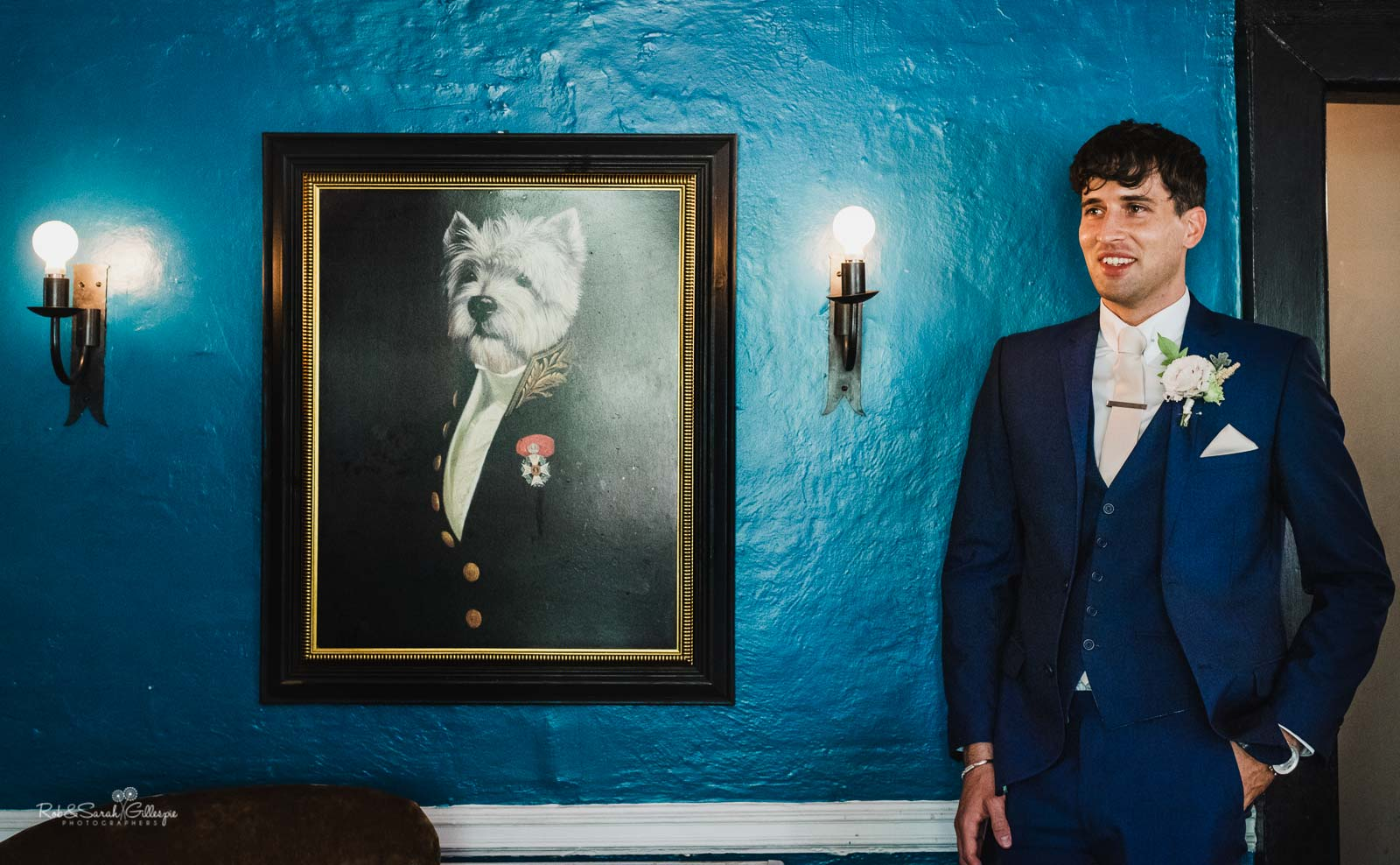 Groom poses for photo next to painting of dog