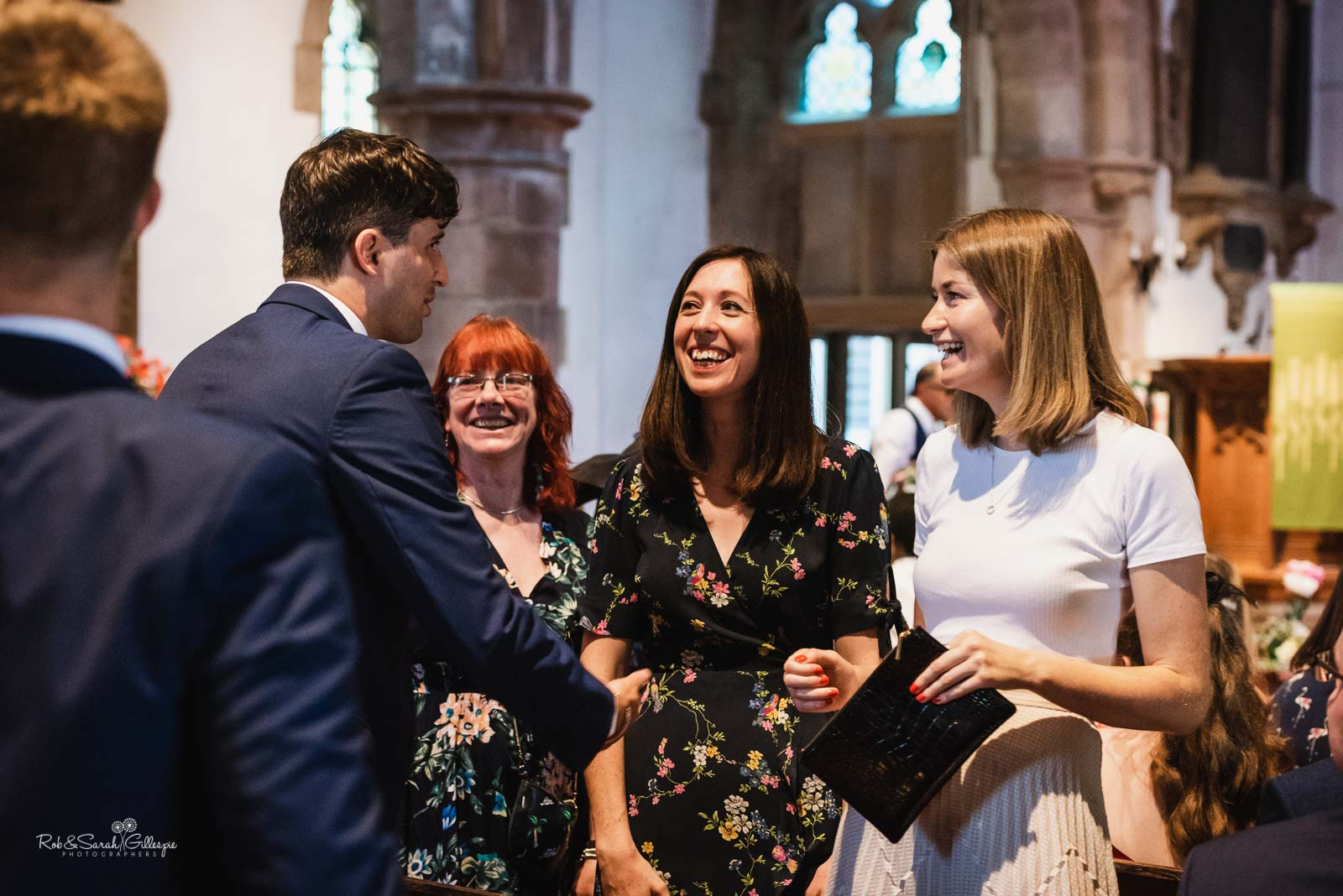 Groom greets wedding guests at Hampton-in-Arden church