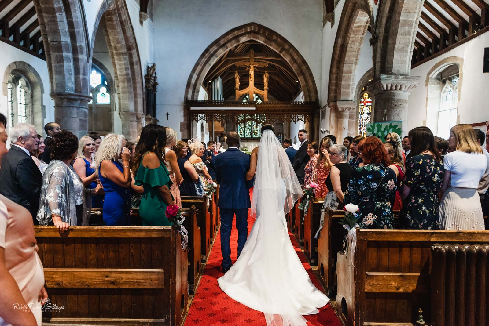 Bride walking up the aisle in Hampton-in-Arden church