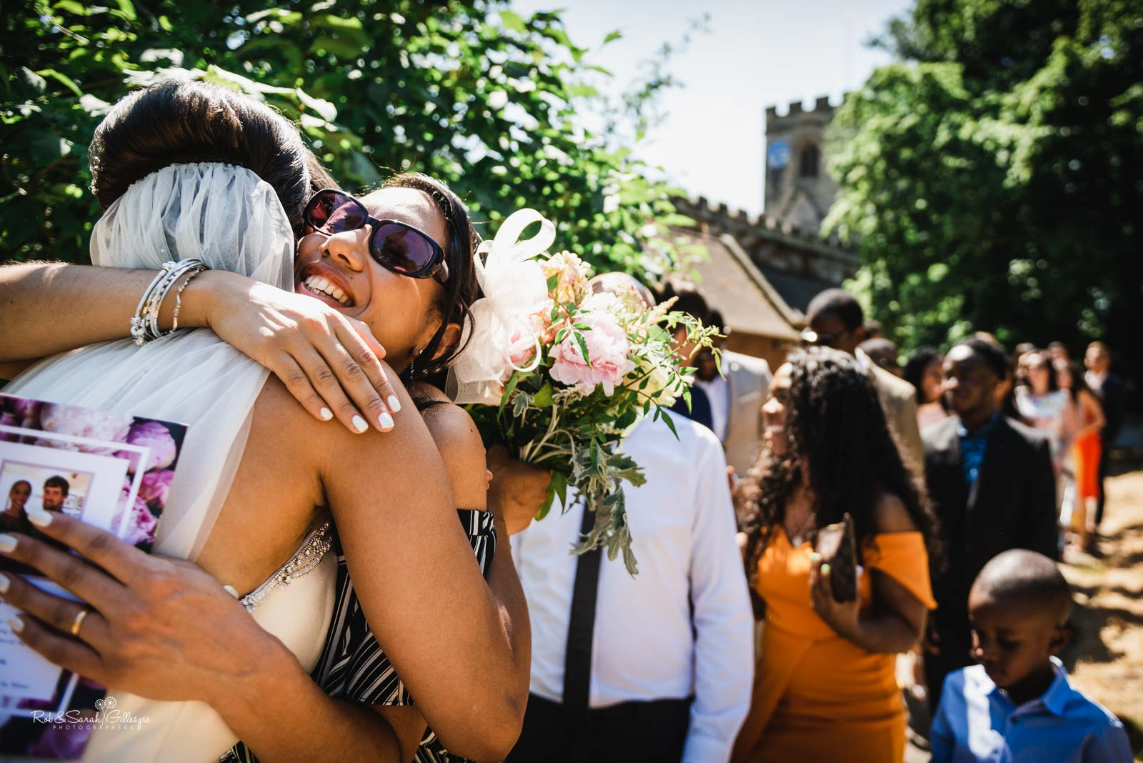 Wedding guests hug bride and groom at Hampton-in-Arden church wedding